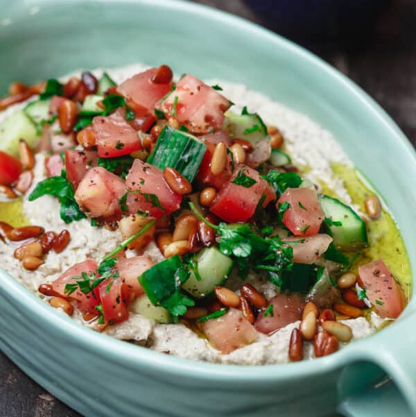 Baba ganoush in dish, topped with tomatoes, cucumbers, parsley and pine nuts.