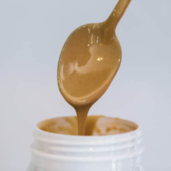 Spoon with tahini pouring into jar